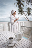 Woman on terrace over sea view. Woman with coffee and mobilephone in hotel terrace over sea view Stock Image