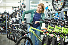 Woman testing bike in sport store Stock Photography