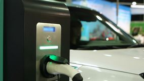 Woman testing e-car, electric vehicle showroom, auto plugged in charging point