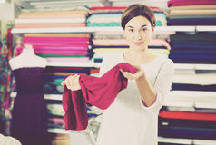 Woman testing fabric quality. Girl customer testing quality of fabric for dress at drapery shop Royalty Free Stock Photography