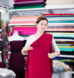 Woman testing fabric quality. Young woman checking quality of fabric for dress at drapery shop Stock Image