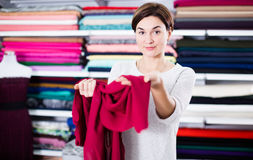 Woman testing fabric quality. Young woman checking quality of fabric for dress at drapery shop Stock Photo