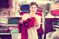 Woman testing fabric quality. Young female shopper examining fabric quality for dress at drapery shop Stock Images