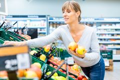 Woman testing the fresh fruit in a supermarket shelf. Holding apples in her hand stock image