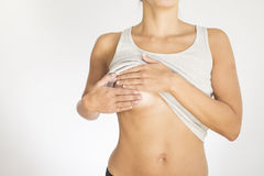 Woman testing her breast for cancer Stock Image