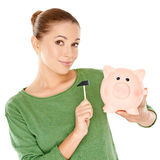 Woman testing her piggy bank with a mallet Royalty Free Stock Images