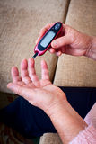 Woman testing for high blood sugar. Stock Photos