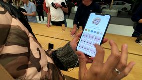 Woman testing new model Iphone XS Max at Apple store, trying to create animoji. San Francisco, USA - September 10, 2018: Woman testing new model Iphone XS Max at stock video footage