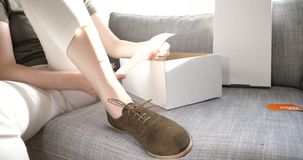 Woman testing new shoes derby style on couch. London, United Kingdom - circa 2018: Elegant woman checking new nubuck leather shoes prices after unboxing on the stock video footage