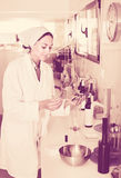 Woman testing wine qualities in industrial chemical laboratory. Cheerful young woman testing wine qualities in industrial chemical laboratory Stock Images
