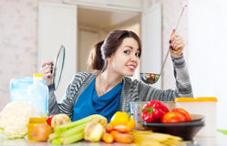 Woman tests food with ladle Stock Photography
