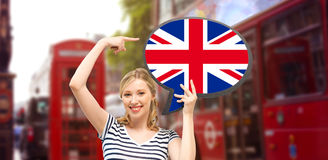 Woman with text bubble of british flag in london. Foreign language, english, travel, people and communication concept - smiling woman holding text bubble of Royalty Free Stock Images