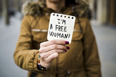 Woman and text I am a free woman. Closeup of a young caucasian woman in the street showing a piece of paper with the text I am a free woman written in it Stock Photography