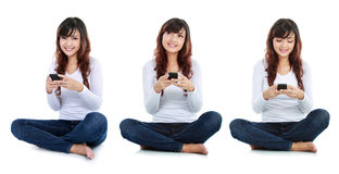 Woman text messaging. Woman sitting on floor and text messaging on a mobile phone while thinking what to say. isolated over white background Royalty Free Stock Photography