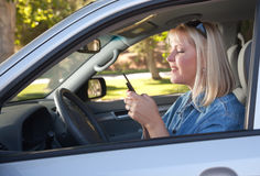 Woman Text Messaging While Driving. Attractive Blonde Woman Text Messaging on Her Cell Phone While Driving Royalty Free Stock Images