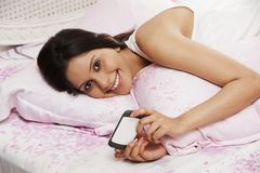 Woman text messaging on a mobile phone on the bed Stock Photography