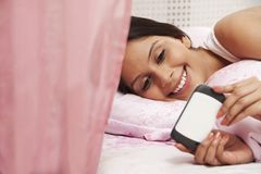 Woman text messaging on a mobile phone on the bed Royalty Free Stock Photography