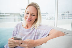 Woman text messaging through mobile phone in living room. Smiling woman text messaging through mobile phone in living room Stock Photography