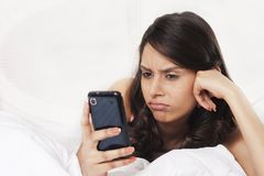 Woman text messaging on mobile phone and looking sad stock image