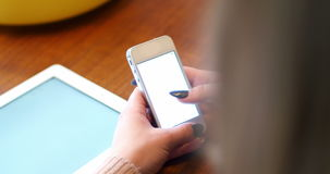 Woman text messaging on mobile phone. Rear view of woman text messaging on mobile phone at home stock footage