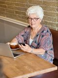 Woman Text Messaging Through Smartphone In Cafe. Senior woman with laptop and coffee cup text messaging through smartphone in cafe Royalty Free Stock Image