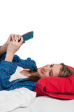 Woman Texting in Bed Stock Photo