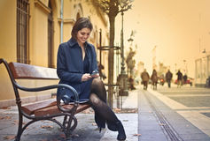 Woman texting on a bench Stock Image