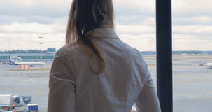 Woman texting on cell and looking at airport area stock video