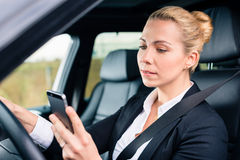 Woman texting while driving by car. Woman texting while driving angrily her car, looking in rage on his phone instead of traffic Royalty Free Stock Images