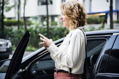 Woman texting before getting into the car royalty free stock photos
