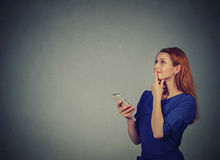 Woman texting on her mobile phone looking up planning. Beautiful woman texting on her mobile phone looking up planning isolated on gray wall background with copy royalty free stock photo
