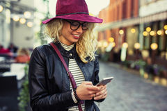 Woman texting on her smartphone. And smiling Royalty Free Stock Image