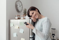 Woman texting in the kitchen Stock Image