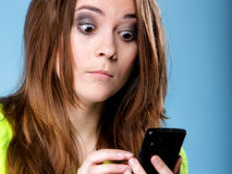Woman texting while looking surprised on phone Stock Photo