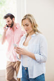 Woman texting messaging while man talking on mobile phone Stock Photography