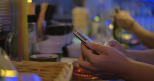 Woman texting on mobile in the bar. Close-up shot of a woman typing message on smartphone at the bar counter stock video footage
