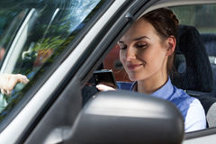 Woman texting on mobile phone during driving a car Royalty Free Stock Images