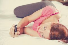 Woman texting on mobile phone reading message laying in bed Stock Photos