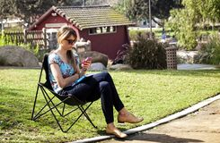 Woman texting at a park Royalty Free Stock Photos
