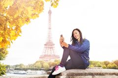 Woman texting on phone against the Eiffel Tower Royalty Free Stock Photo