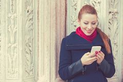Woman texting on a phone. Casual urban girl using smartphone smiling happily outdoors stock photos