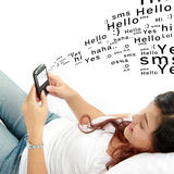 Woman texting on phone lying on bed Royalty Free Stock Photos