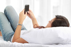 Woman texting on phone lying on bed Royalty Free Stock Photo