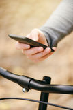 Woman texting on phone while riding bicycle Stock Image