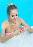 Woman texting in the pool Stock Photography