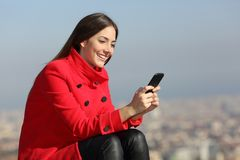 Woman texting on smart phone in winter with city in background. Happy woman in red texting on smart phone in winter with a city in background stock photo
