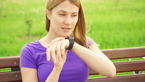 Woman texting on smart watch in park. Using her smartwatch, sending message to friend with speaking app. Active sportive woman with bike texting on smart watch stock video