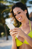 Woman texting on smartphone at the beach Stock Photo