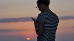 Woman texting on smartphone on the beach during sunset. Slow motion. Professional shot in 4K resolution. 101. You can use it e.g. in your commercial video stock video