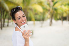 Woman texting on smartphone during caribbean travel vacation Stock Image